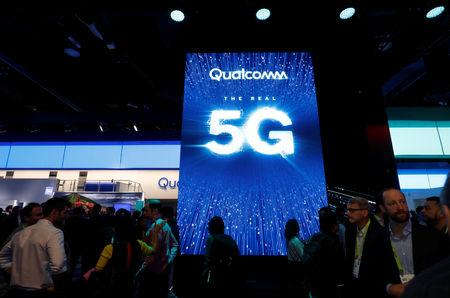 FILE PHOTO: People walk by a video display promoting 5G connectivity at the Qualcomm booth during the 2019 CES in Las Vegas, Nevada, U.S. January 8, 2019. REUTERS/Steve Marcus