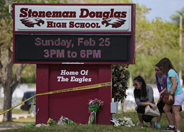 Mourners bring flowers as they pay tribute at a memorial for the victims of the shooting at Marjory Stoneman Douglas High School. (Getty)