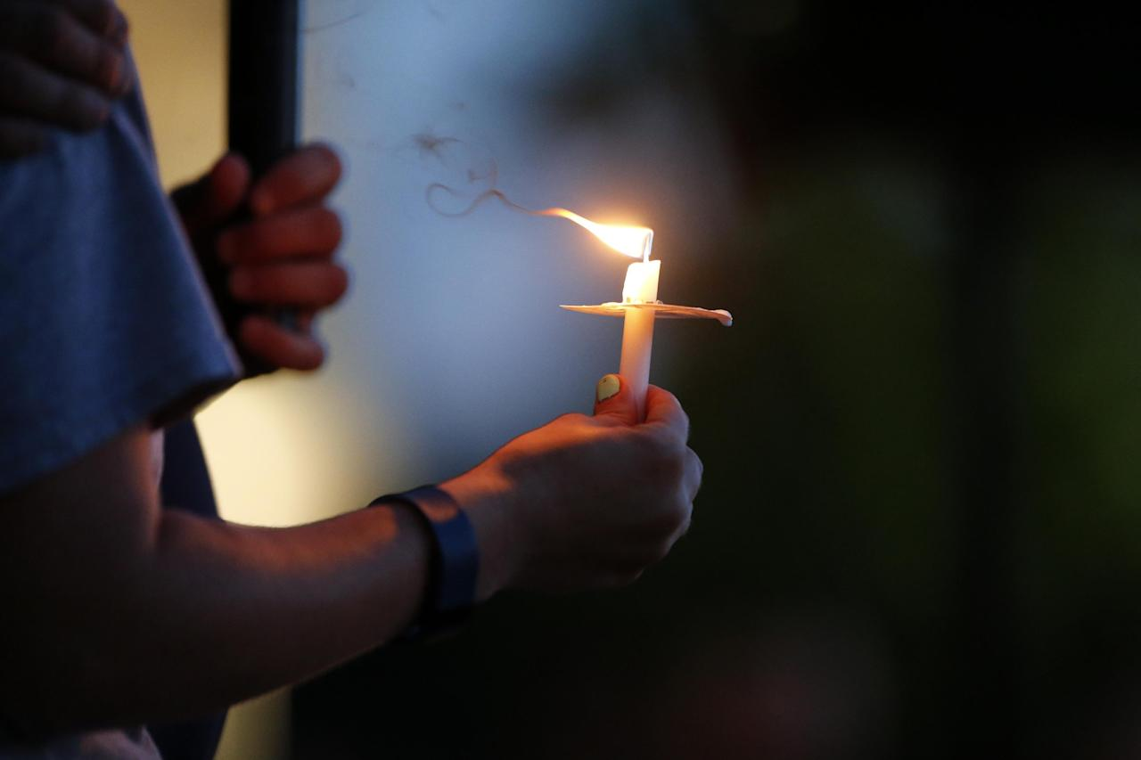 People attend a candlelight vigil for fallen Baton Rouge police officers, at the Healing Place Church in Baton Rouge, La., Monday, July 18, 2016. Multiple police officers were killed and wounded Sunday morning in a shooting near a gas station in Baton Rouge. (AP Photo/Gerald Herbert)