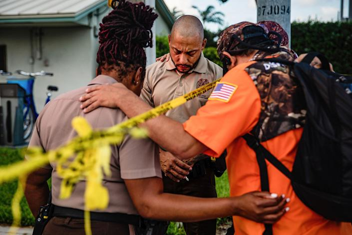 """Members of a Christian mens group pray with Miami-Dade Police Department officers outside the Champlain Towers South collapse site on June 26.<span class=""""copyright"""">Scott McIntyre—The New York Times/Redux</span>"""