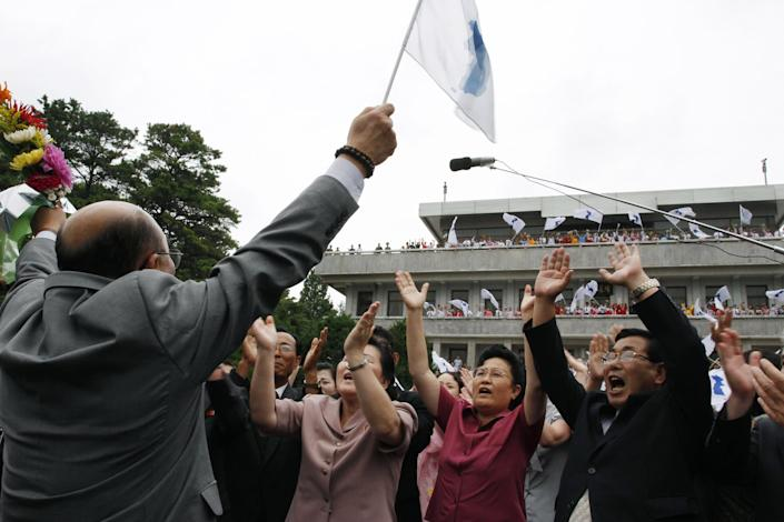 Activist No Su-hui, left, waves a flag depicting a unified Korean Peninsula to a crowd of North Korean supporters, before crossing the demarcation line into South Korea, at the Demilitarized Zone at Panmunjom, Korea, on Thursday, July 5, 2012. No crossed into South Korea and was immediately detained by South Korean officials for making an extended trip to Pyongyang without South Korean government approval as required by law. (AP Photo/Kim Kwang Hyon)