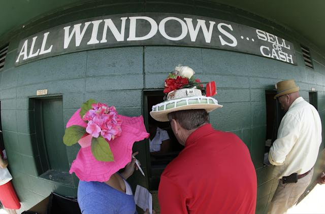 Fans make wagers before the 140th running of the Kentucky Derby horse race at Churchill Downs Saturday, May 3, 2014, in Louisville, Ky. (AP Photo/Charlie Riedel)
