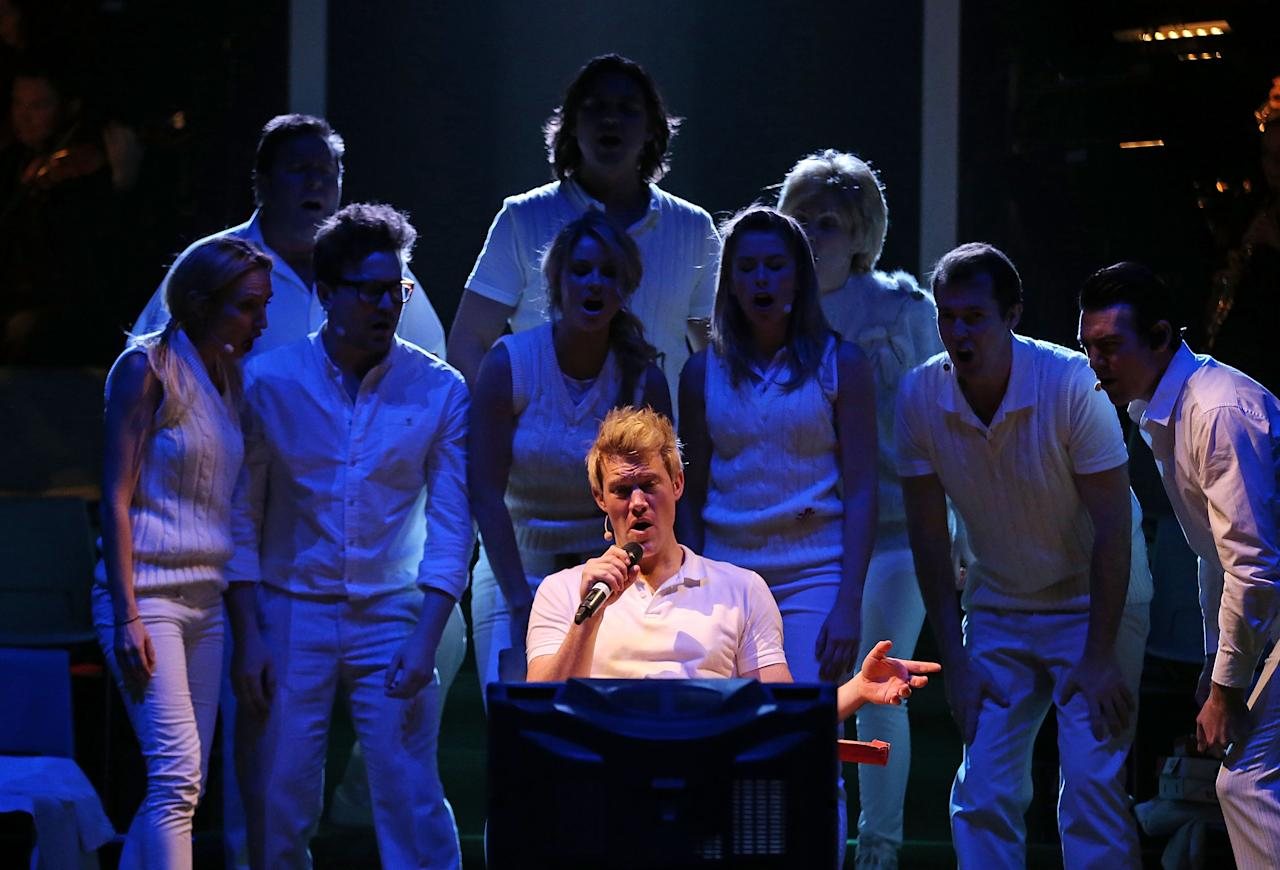 """MELBOURNE, AUSTRALIA - JUNE 20:  Eddie Perfect who plays Shane Warne sings as he watches television during a """"Shane Warne The Musical' media call at the Arts Centre Melbourne on June 20, 2013 in Melbourne, Australia. Shane Warne The Musical is a musical comedy based on the life of Australian cricketer Shane Warne.  (Photo by Scott Barbour/Getty Images)"""