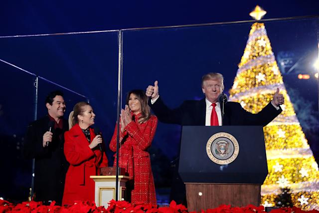 U.S. first lady Melania Trump, with U.S. President Donald Trump and hosts Dean Cain (L) and Kathie Lee Gifford (2nd L), reacts after she pressed the button to light the tree during the National Christmas Tree lighting ceremony near the White House in Washington, U.S. November 30, 2017. REUTERS/Jonathan Ernst