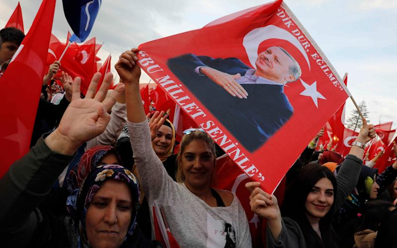 Supporters of Turkish President Erdogan wave national flags as they wait for his arrival at the Presidential Palace in Ankara - Credit: REUTERS/Umit Bektas