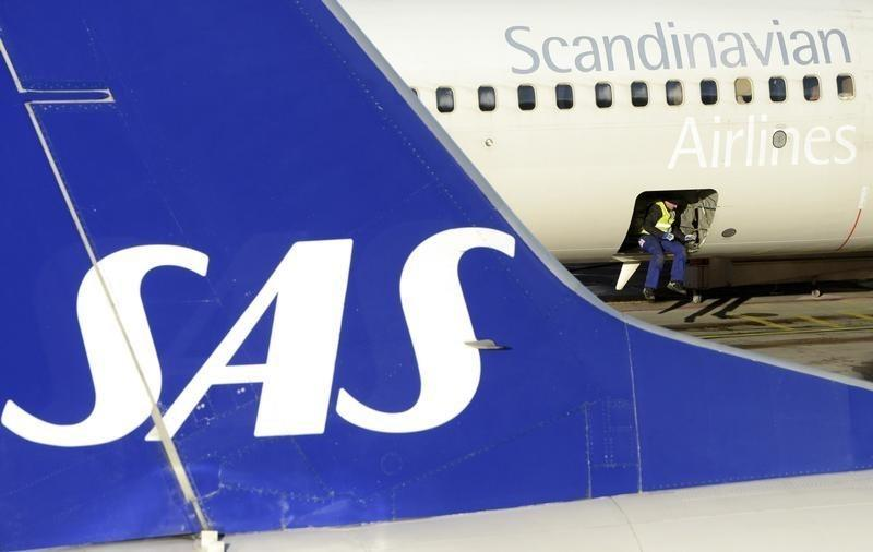 A loader sits in the cargo bay of an SAS Boeing 737 aircraft parked at Arlanda airport's Terminal Five, north of Stockholm