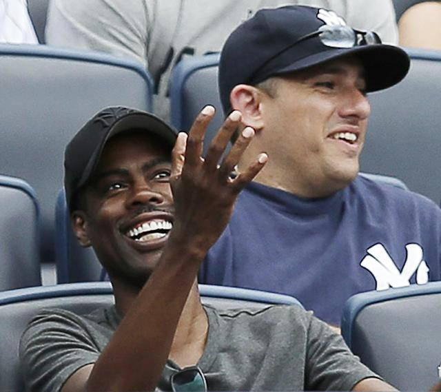 CORRECTS ASTROS BATTER TO JON SINGLETON, NOT MARWIN GONZALEZ - Comedian Chris Rock, left, reacts after catching a foul ball off Houston Astros' Jon Singleton in the seventh inning of a baseball game against the New York Yankees 2wld2at Yankee Stadium in New York, Thursday, Aug. 21, 2014. (AP Photo/Kathy Willens)