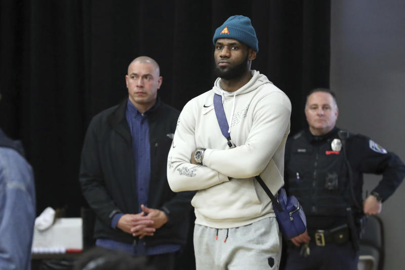 In this Monday, Jan. 20, 2020, photo, Los Angeles Lakers NBA basketball player LeBron James watches a high school basketball game between his son's team, Sierra Canyon, and Paul VI at the Hoophall Classic in Springfield, Mass. (AP Photo/Gregory Payan)