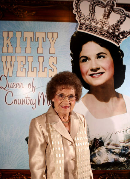 """FILE - This Aug. 14, 2008 file photo originally released by the Country Music Hall of Fame and Museum shows music pioneer Kitty Wells at an exhibit honoring her career in Nashville, Tenn. Wells, the first female superstar of country music, has died at the age of 92. The singer's family says Wells died at her home Monday after complications from a stroke. Her recording of """"It Wasn't God Who Made Honky Tonk Angels"""" in 1952 was the first No. 1 hit by a woman soloist on the country music charts. Other hits included """"Making Believe"""" and a version of """"I Can't Stop Loving You."""" (AP Photo/Country Music Hall of Fame and Museum, Donn Jones, file)"""