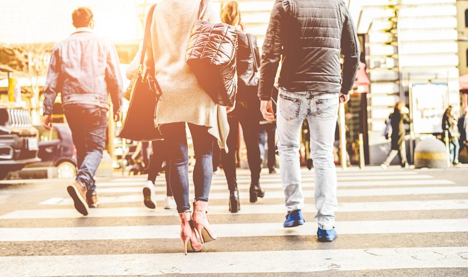 Crowd of people walking on zebra crossing street city center - Concept of modern, rushing, urban, city life, business, shopping - Focus on woman black bag