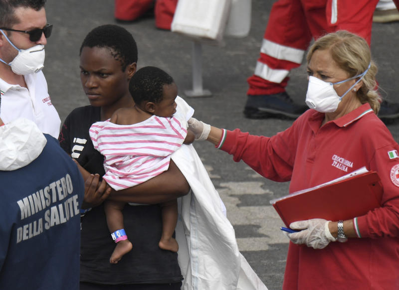 """A migrant woman and baby wait for a health check up after disembarking from Italian Coast Guard vessell """"Diciotti"""" which docked at the Sicilian port of Catania, southern Italy, Wednesday, June 13, 2018. The vessel docked in Catania with 932 migrants aboard in a sign that Italy under the populist 5-Star Movement and anti-migrant League is still accepting some migrants, but is forcing other countries to share the burden. (AP Photo/Salvatore Cavalli)"""