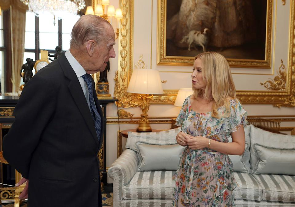 WINDSOR, UNITED KINGDOM - APRIL 04: Prince Philip, Duke of Edinburgh, Patron of the Britain-Australia Society, presents Kylie Minogue with the Britain-Australia Society Award for 2016 during a private audience in the White Drawing Room at Windsor Castle on April 4, 2017 in Windsor, United Kingdom.. The Britain-Australia Award recognises Australian and British individuals who have made a significant contribution to the Australia-UK bilateral relationship. Past recipients include Barry Humphries, and the Rt Hon Lord Hague PC.  (Photo by Steve Parsons - WPA Pool/Getty Images)
