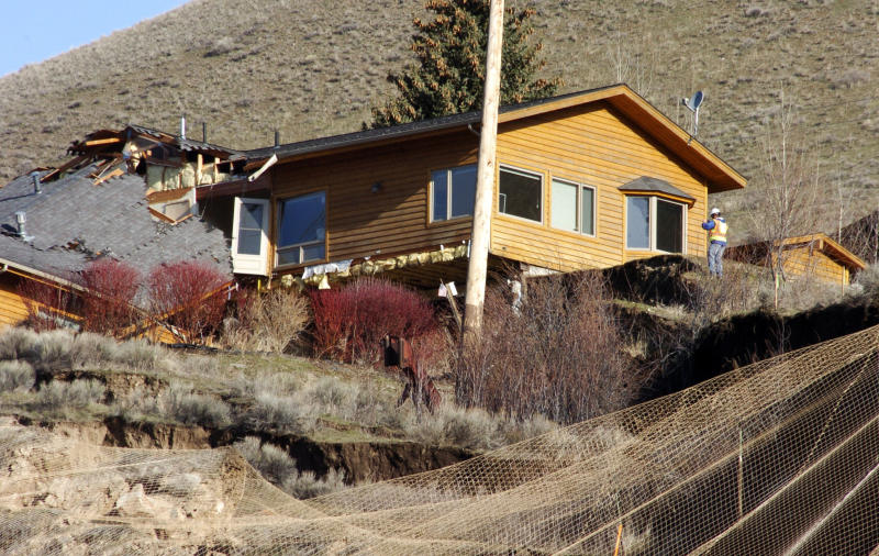 A worker inspects damage to a house at the top of a slow-motion landslide in Jackson, Wyo., on Saturday, April 19, 2014. No one can say when the mountainside collapsing into this Wyoming resort town will give way. But it appears increasingly likely that when it does, it's going to take a piece of Jackson with it. (AP Photo/Matthew Brown)
