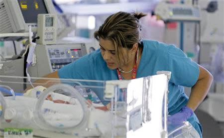 A nurse attends to an infant in the neonatal intensive care unit of the Holtz Children's Hospital at Jackson Memorial Hospital in Miami