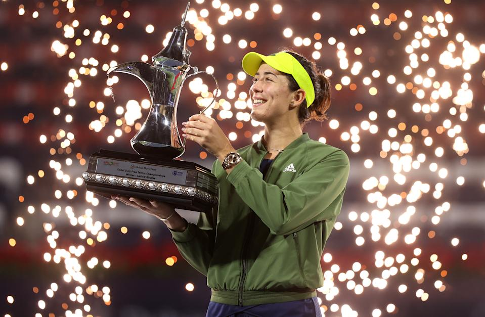 DUBAI, UNITED ARAB EMIRATES - MARCH 13: Garbine Muguruza of Spain celebrates with the trophy following victory during the Dubai Duty Free Tennis Women's Final match between Barbora Krejcikova and Garbine Muguruza on Day Seven of the Dubai Duty Free Tennis at Dubai Duty Free Tennis Stadium on March 13, 2021 in Dubai, United Arab Emirates. (Photo by Francois Nel/Getty Images)