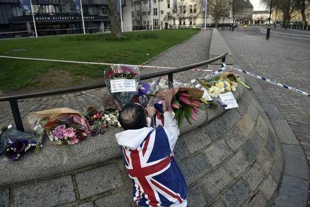 A man wears a Union Flag sweatshirt near the Houses of Parliament in Westminster the day after an attack, in London