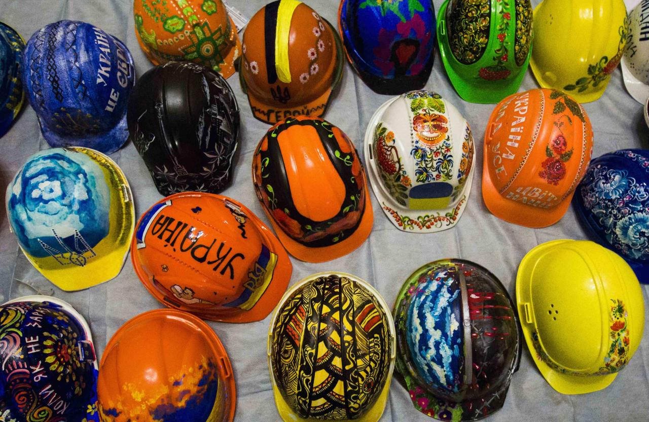 """A collection of hardhats painted with motifs for anti-government protesters, are on display at the Kiev City Hall, which has been occupied by opposition forces, February 1, 2014. Anatoly Kravets, the coordinator of an impromptu art project asking protesters to adorn the hardhats they used to protect themselves during street battles with riot police, said the variety of motifs reflect the diversity of Ukrainians who have joined on the movement around Kiev's Independence Square. """"Those helmets have become the symbol of our revolution, they are the symbol of the peaceful coming together of our nation. They protect us and their colorful appearance contrasts nicely the black uniformity of police helmets,"""" he said. REUTERS/Thomas Peter (UKRAINE - Tags: POLITICS CIVIL UNREST ENTERTAINMENT SOCIETY)"""