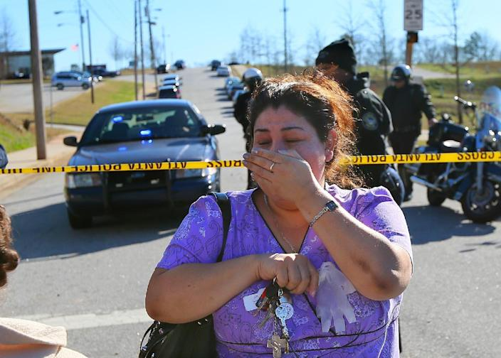 A distraught woman is turned back by police at the scene of a school shooting at Price Middle school in Atlanta on Thursday, Jan. 31, 2013. A 14-year-old boy was wounded outside the school Thursday afternoon and a fellow student was in custody as a suspect, authorities said. No other students were hurt. (AP Photo/Atlanta Journal-Constitution, Curtis Compton) MARIETTA DAILY OUT; GWINNETT DAILY POST OUT; LOCAL TV OUT; WXIA-TV OUT; WGCL-TV OUT