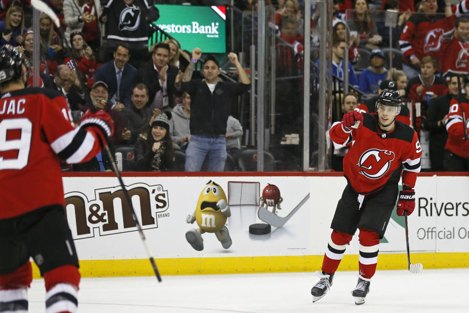 New Jersey Devils left wing Nikita Gusev (97) celebrates towards Devils center Travis Zajac after Zajac scored a goal against the Tampa Bay Lightning during the second period of an NHL hockey game Sunday, Jan. 12, 2020, in Newark, N.J. (AP Photo/Adam Hunger)