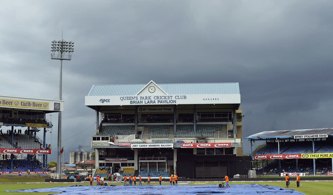 Groundsmen work to remove water from the field after a rain during the sixth match of the Tri-Nation series between India and Sri Lanka at the Queen's Park Oval stadium in Port of Spain on July 9, 2013. The match is at halt due to rain. AFP PHOTO/Jewel Samad