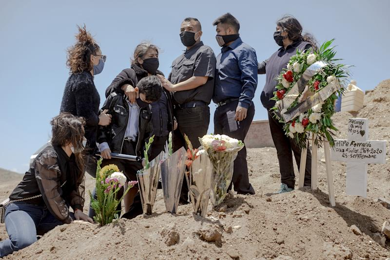 A family wearing protective masks mourns during the burial of a relative who died from coronavirus at Municipal Cemetery No. 13 in Tijuana, Mexico, on May 12. | Fred Ramos—Bloomberg/Getty Images