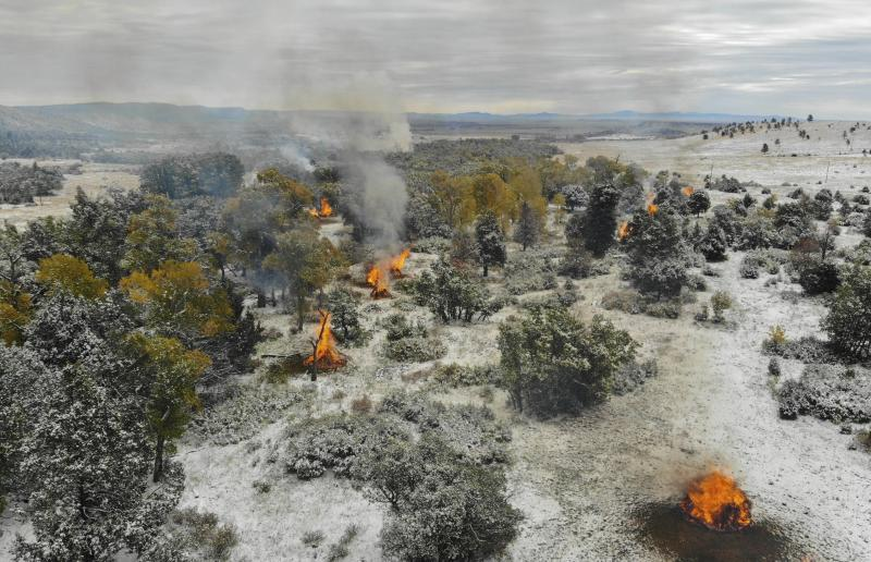 This Oct. 15, 2018, photo, provided by Philmont Scout Ranch shows piles of slash being burned as part of an effort to clear out extra fuel. The historic ranch near Cimarron, New Mexico, is rebuilding following a devastating wildfire that burned nearly 44 square miles in 2018. Backcountry trails were wiped out along with trail camps. (Philmont Scout Ranch via AP)