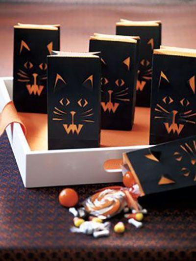 """<p>Make a candy presentation that doubles as a temporary decoration.</p><p><a href=""""https://www.womansday.com/home/crafts-projects/how-to/a5875/halloween-craft-how-to-cat-face-treat-bags-123825/"""" rel=""""nofollow noopener"""" target=""""_blank"""" data-ylk=""""slk:Get the tutorial for Cat Face Treat Bags."""" class=""""link rapid-noclick-resp""""><em>Get the tutorial for Cat Face Treat Bags.</em></a></p>"""