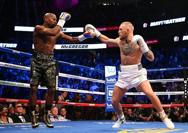 <p>Conor McGregor moves in against Floyd Mayweather Jr. in the first round at T-Mobile Arena. Mandatory Credit: Mark J. Rebilas-USA TODAY Sports </p>