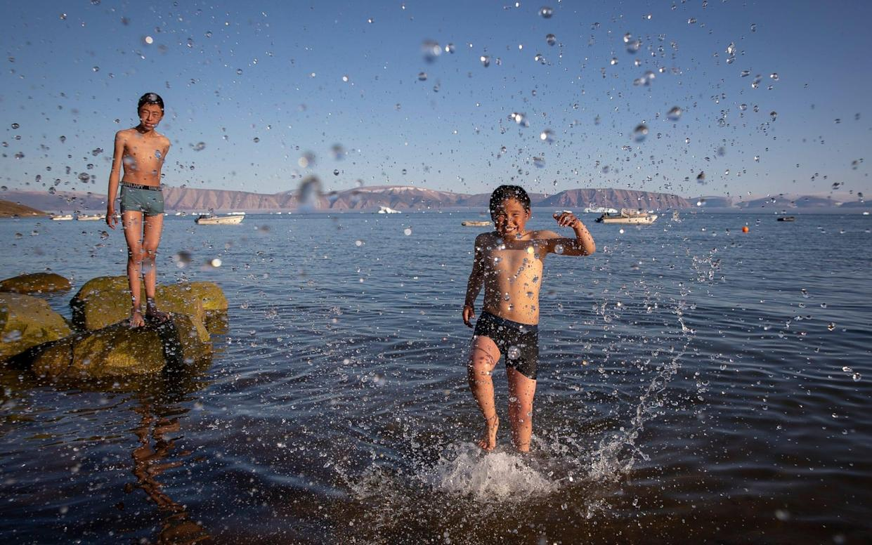 Teenage boys pictured enjoing the recent heatwave by taking a dip in the sea in Qaanaaq, one of Greenland's most northernly towns and settlements - Daily Mirror