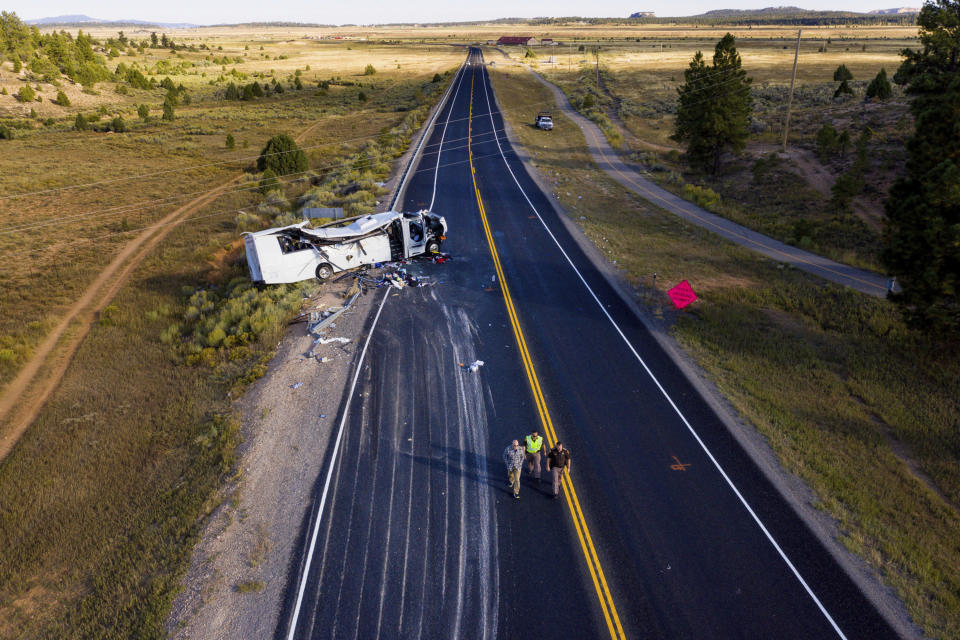 FILE - In this Sept. 20, 2019, file photo, the remains of a bus that crashed while carrying Chinese-speaking tourists lie along State Route 12 near Bryce Canyon National Park in Utah. The families of Chinese tourists killed or injured in the 2019 tour bus crash say the state's design and maintenance failed to keep the remote highway safe. More than a dozen people were thrown from the bus when the driver drifted off the road and overcorrected when he steered back, sending the bus into a rollover. A lawsuit alleges the state failed to post warning signs, had a road design that left little room for error and included no rumble strip to warn drivers. The Utah Department of Transportation declined to comment. U.S. regulators have previously ruled out highway design, signage and other characteristics as factors. (Spenser Heaps/The Deseret News via AP, File)