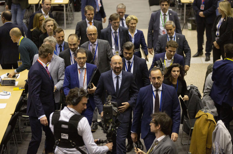 European Council President Charles Michel, center, walks to a media conference during an EU summit in Brussels, Friday, Dec. 13, 2019. European Union leaders gathered for their year-end summit and discussed climate change funding, the departure of the UK from the bloc and their next 7-year budget. (AP Photo/Virginia Mayo)