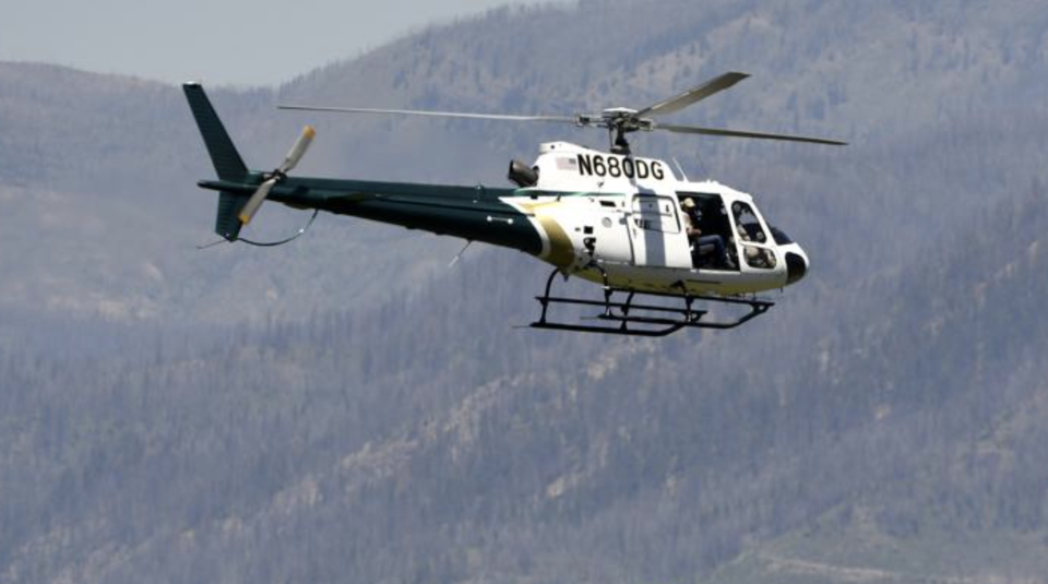A helicopter from Montana Fish, Wildlife and Parks flies around the Ovando, Mont., area in search of a bear that killed a camper early that morning. Source: Tom Bauer/The Missoulian via AP