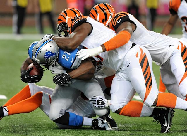 Detroit Lions running back Reggie Bush (21) is stopped by Cincinnati Bengals defensive tackle Geno Atkins, middle and defensive end Michael Johnson, right, in the first quarter of an NFL football game against Sunday, Oct. 20, 2013, in Detroit. (AP Photo/Jose Juarez)