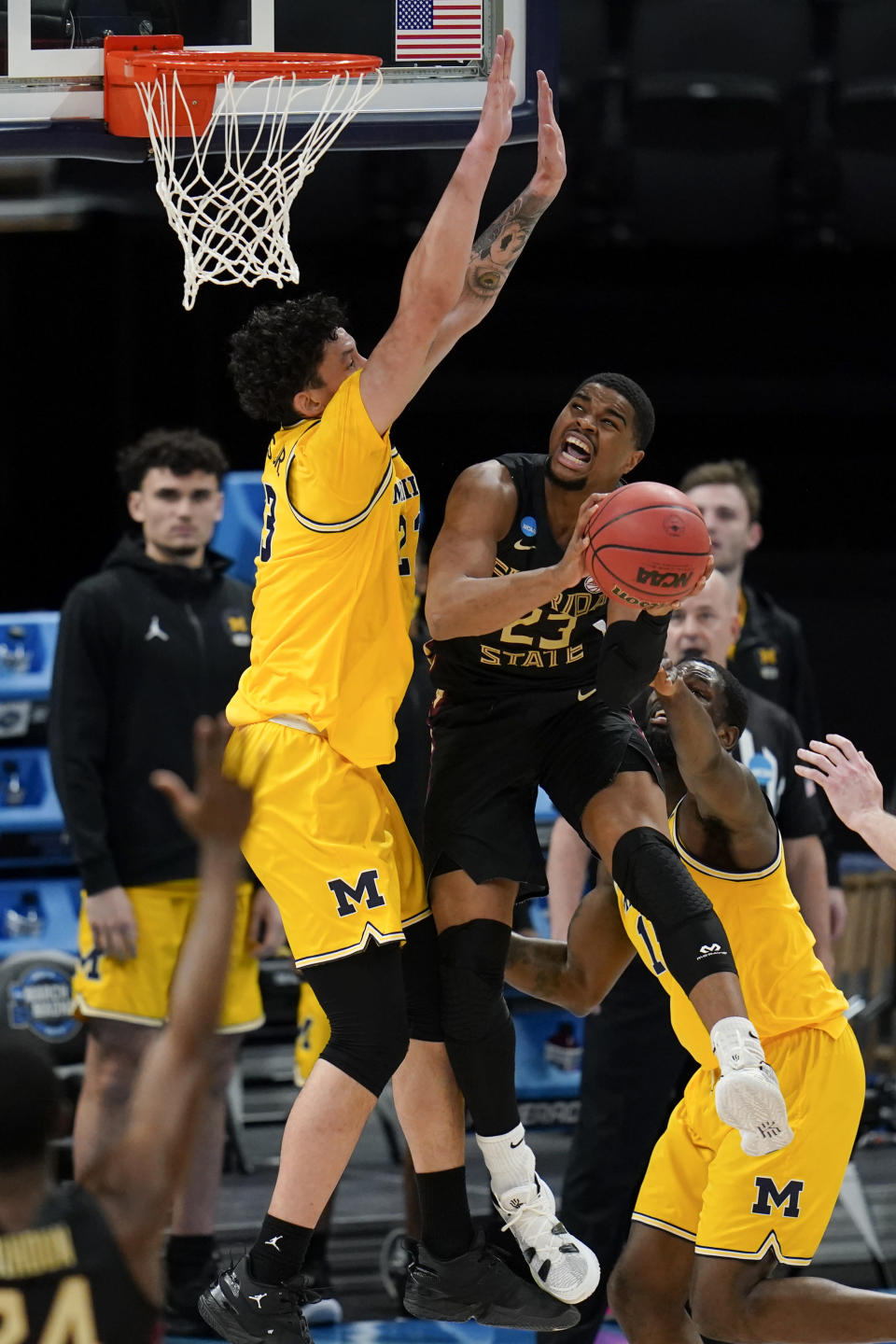 Florida State guard M.J. Walker, right, looks to shoot over Michigan forward Brandon Johns Jr., left, during the first half of a Sweet 16 game in the NCAA men's college basketball tournament at Bankers Life Fieldhouse, Sunday, March 28, 2021, in Indianapolis. (AP Photo/Jeff Roberson)