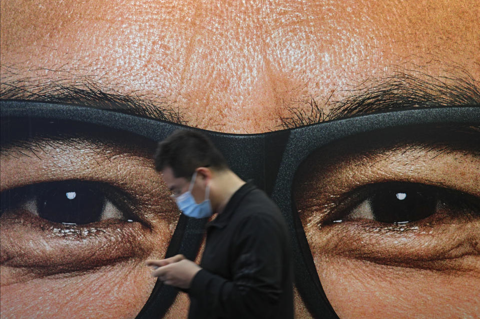 A man wearing a face mask to help curb the spread of the coronavirus walks by an advertisement featuring a human eyes at a subway station in Beijing, Sunday, March 21, 2021. (AP Photo/Andy Wong)