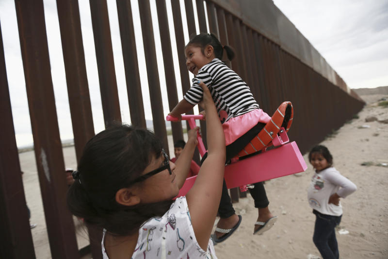 CORRECTS THE FIRST NAME OF THE PROFESSOR TO RONALD, NOT RONALDO AND THE LAST NAME OF THE PHOTOGRAPHER TO CHAVEZ, NOT TORRES - A woman with her little girls helps them play seesaw installed between the border fence that divides Mexico from the United States in Ciudad de Juarez, Mexico, Sunday, July 28, 2019. The seesaw was designed by Ronald Rael, a professor of architecture in California. (AP Photo/Christian Chavez)