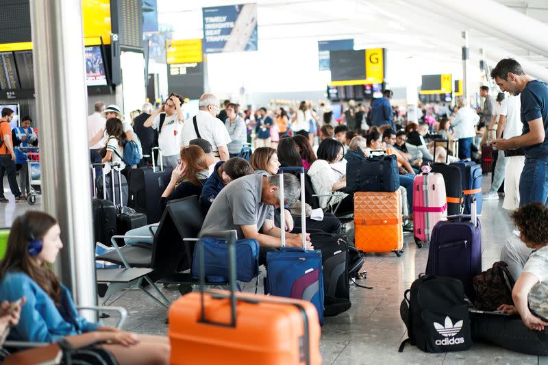 FILE PHOTO: People wait inside Terminal 5 at Heathrow Airport as IT problems caused delays in London