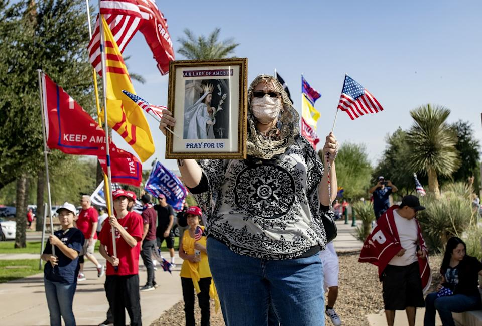 "Trump supporter Elizabeth Lund holds her rosary and a religious photo at a ""Stop The Steal"" rally in Phoenix."