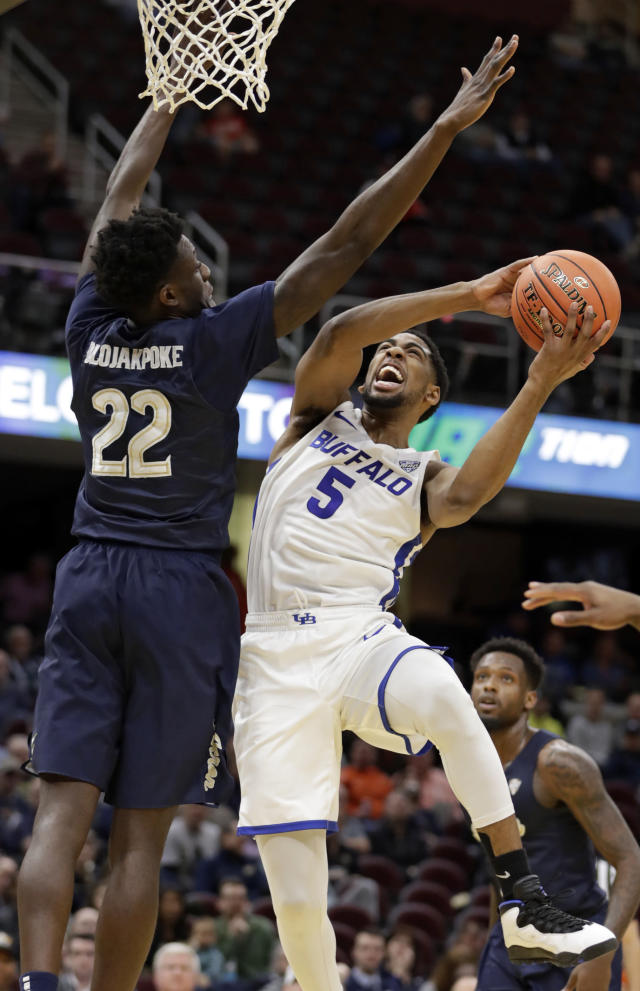 Buffalo's CJ Massinburg (5) drives to the basket against Akron's Emmanuel Olojakpoke (22) during the first half of an NCAA college basketball game at the Mid-American Conference tournament, Thursday, March 14, 2019, in Cleveland. (AP Photo/Tony Dejak)