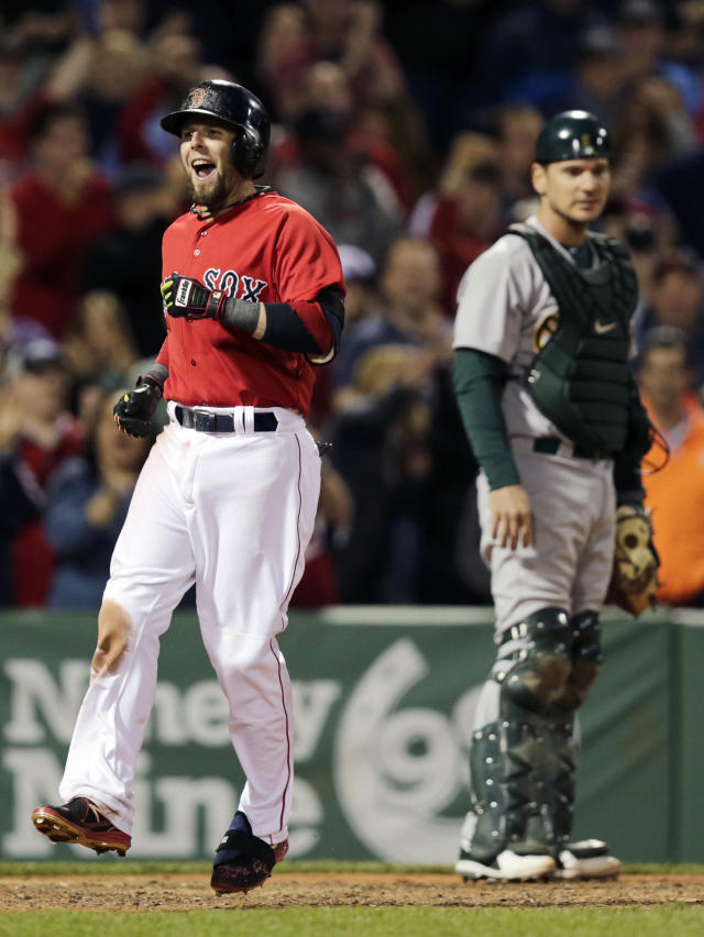 Boston Red Sox's Dustin Pedroia celebrates as he passes Oakland Athletics catcher John Jaso while crossing home plate on his grand slam during the sixth inning of a baseball game at Fenway Park in Boston, Friday, May 2, 2014. (AP Photo/Charles Krupa)
