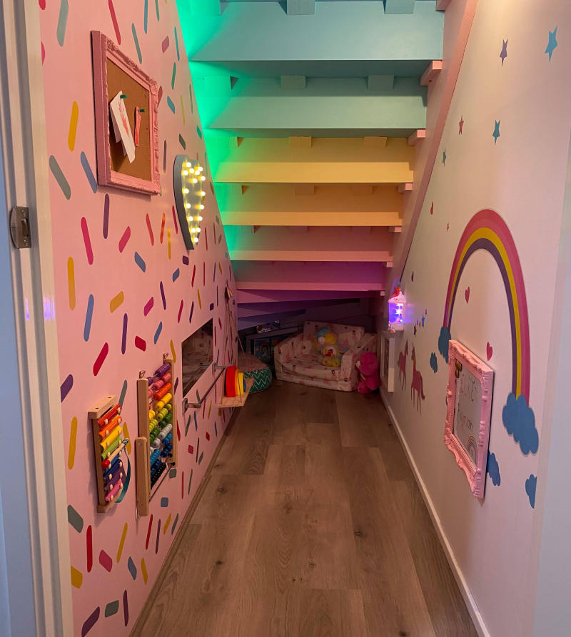 Under stair space transformed in pink and rainbow playroom with Kmart LED lights