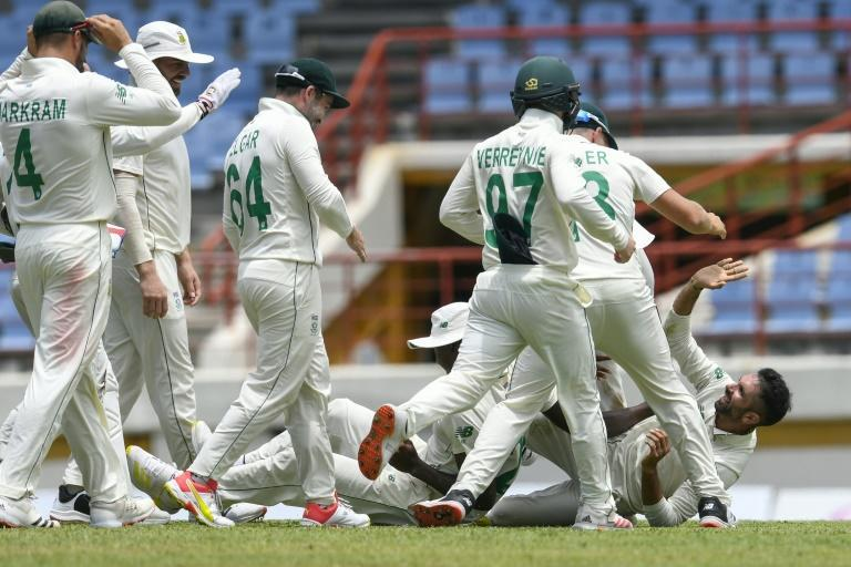 Keshav Maharaj (R) is engulfed by his teammates in St Lucia after becoming only the second South Africa bowler to take a hat-trick in Test cricket
