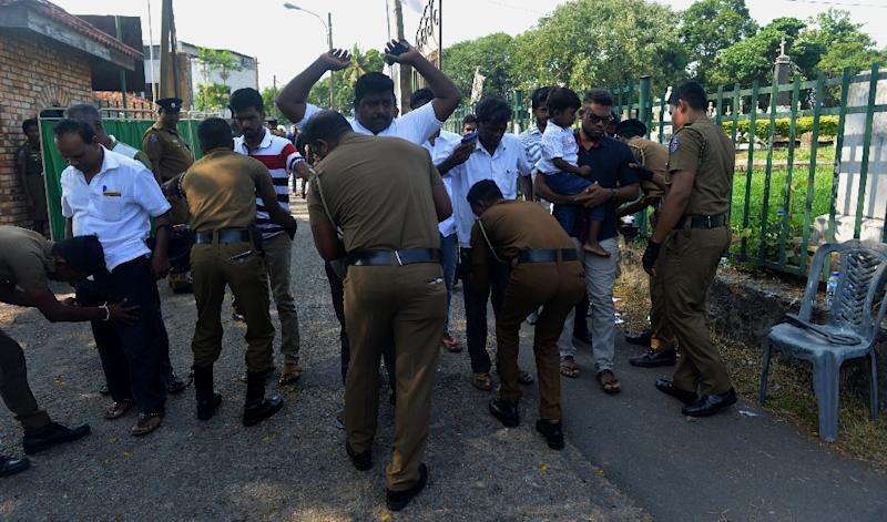 Sri Lankan policemen carry out a security check on men attending a funeral ceremony for a bomb blast victim in Colombo