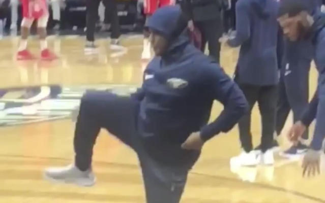 Pelicans fan Tony Roberts gets some light stretching in on the sidelines.