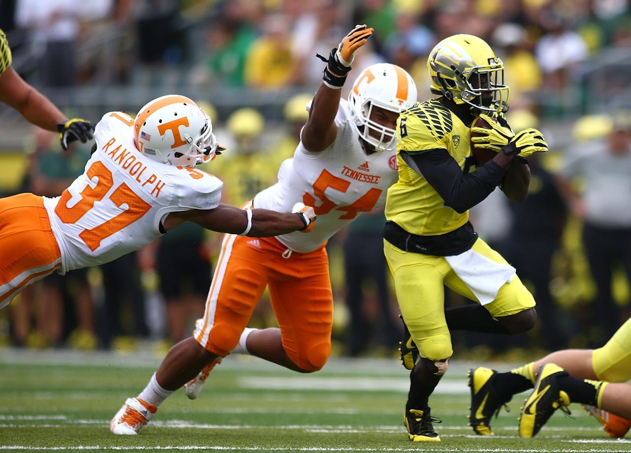 EUGENE, OR - SEPTEMBER 14: De'Anthony Thomas #6 of the Oregon Ducks runs the ball against Brian Randolph #37 and Jordan Williams #54 of the Tennessee Volunteers on September 14, 2013 at the Autzen Stadium in Eugene, Oregon. (Photo by Jonathan Ferrey/Getty Images)