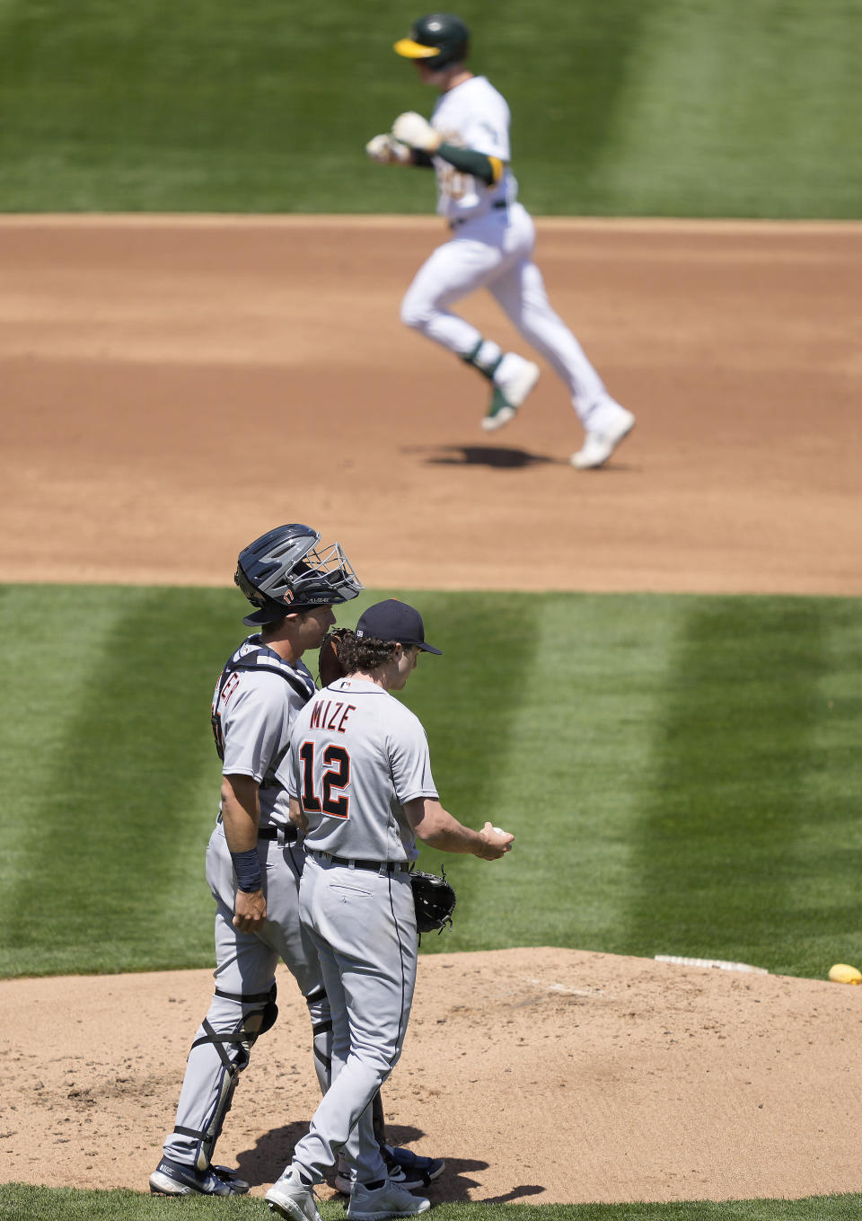 Detroit Tigers pitcher Casey Mize (12) and catcher Grayson Greiner (17) talk on the mound as Oakland Athletics' Mark Canha, top, rounds the bases after hitting a solo home run during the second inning of a baseball game on Saturday, April 17, 2021, in Oakland, Calif. (AP Photo/Tony Avelar)