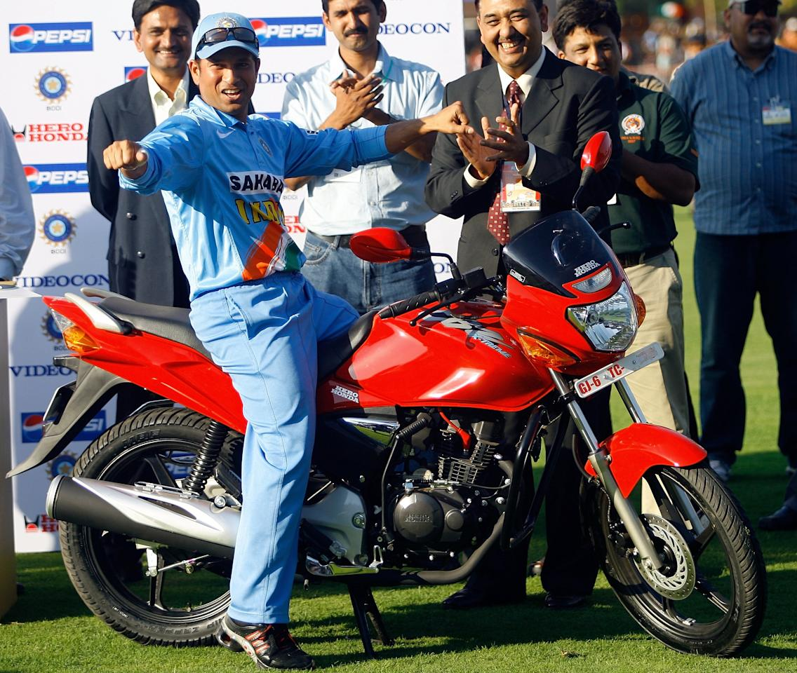Indian cricketer Sachin Tendulkar gestures while posing with his Man of the Series prize - a motorbike - during the prize-giving ceremony after the fourth One Day International (ODI) match against the West Indies in Vadodara, 31 January 2007.  India won the four match ODI series by 3-1.  AFP PHOTO/ Indranil MUKHERJEE