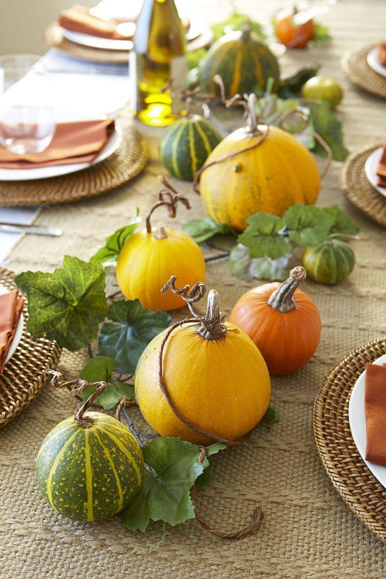 <p>Fill out a row of decorative gourds by weaving in a faux ivy garland. Take this two-step project to the next level by curling wire vines around pumpkin stems.</p>