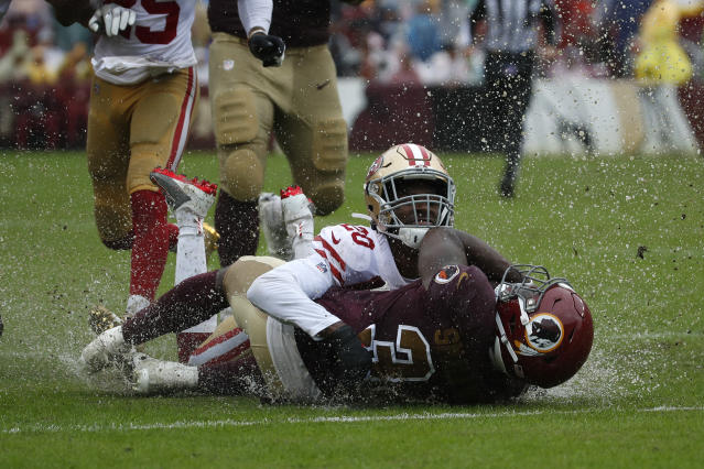 Rain water splashes as San Francisco 49ers cornerback Jimmie Ward (20) tackles Washington Redskins running back Wendell Smallwood in the first half of an NFL football game, Sunday, Oct. 20, 2019, in Landover, Md. (AP Photo/Alex Brandon)