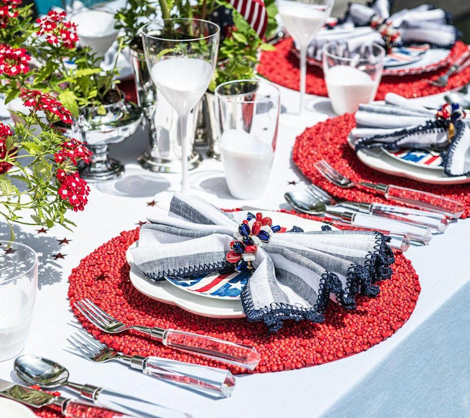 """<p><strong><strong>What will your Fourth of July gathering look like this year?</strong></strong></p><p>This year, I'll be celebrating with an outdoor BBQ around the pool surrounded by friends and family. To make sure everyone has the opportunity to catch the late-night fireworks, I love having everyone over in the early afternoon. We start off with cocktails around the pool where everyone catches up and afterwards sit down for an early dinner. Before everyone heads out I love lighting sparklers, ending the evening with fun for all.<strong><br></strong></p><p><strong>How will you be setting your Fourth of July table?</strong><br><br> I'll start this year's table with an ombre tablecloth in light blue which brings an airiness to the setting and is perfect near the pool. Since it is a Fourth of July celebration, red, white and blue are a must. However, I love incorporating these colors in an elevated way. </p><p>As a nod to the holiday, I'll be using red, intricately beaded placemats, along with soft, blue linen napkins and handblown glassware with a white finish. I'll complete the table with a warm and inviting centerpiece with subtle touches of miniature flags and confetti. </p><p><em>Shop the Look: Tablecloth, <a href=""""https://kimseybert.com/products/dip-dye-tablecloth-in-white-periwinkle"""" rel=""""nofollow noopener"""" target=""""_blank"""" data-ylk=""""slk:Kim Seybert"""" class=""""link rapid-noclick-resp"""">Kim Seybert</a></em></p>"""